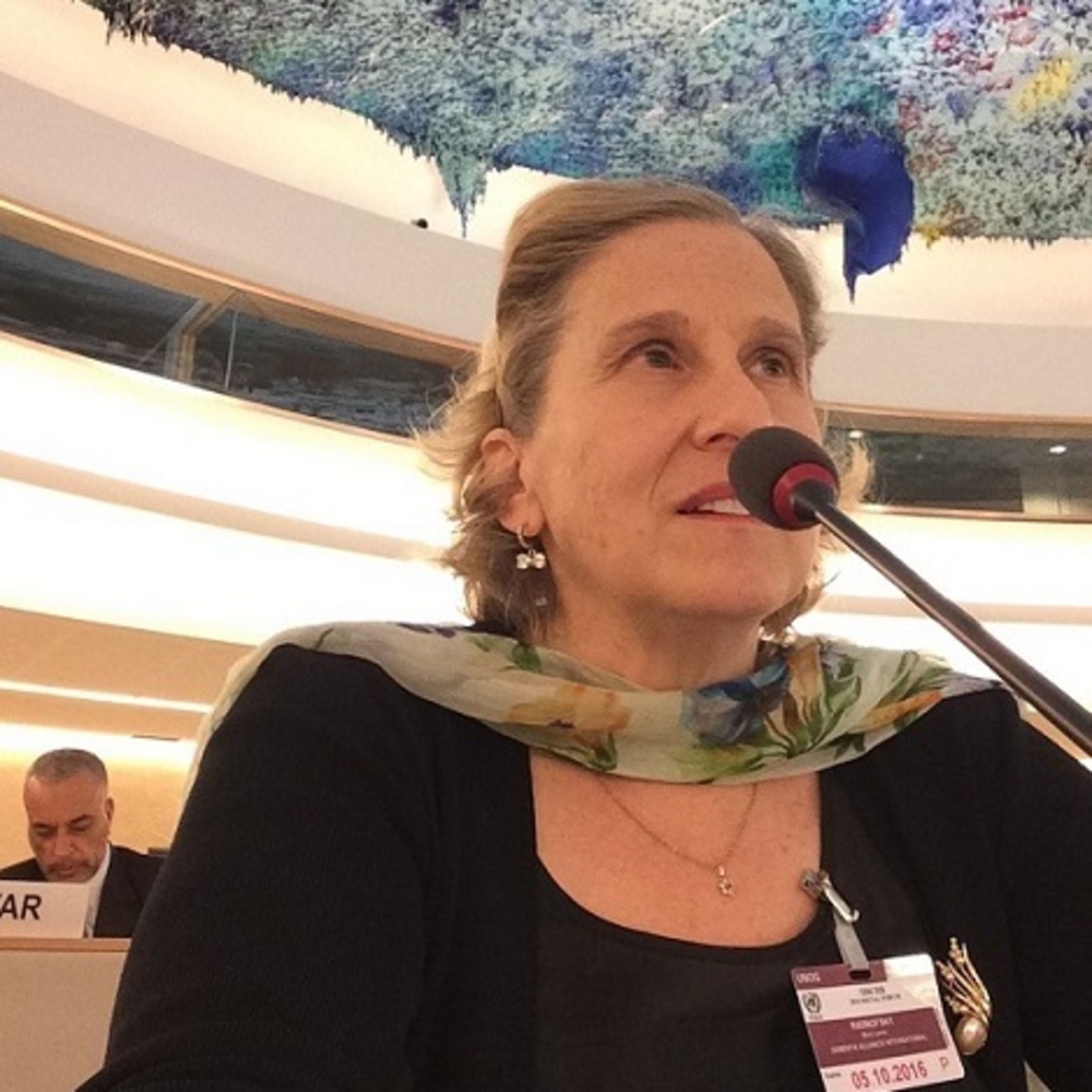 Mary with a gauzy scarf and a conference-type badge speaking into a microphone.